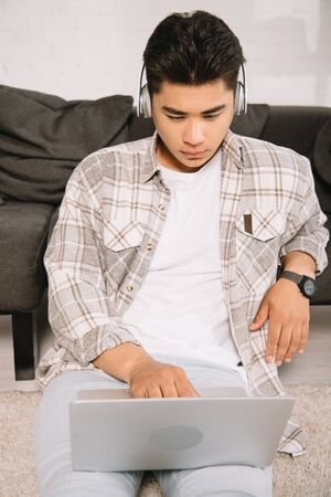 attentive asian man in headphone using laptop while sitting on floor at home Foto de archivo - 132005196