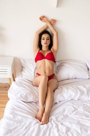 full length view of sexy girl in red underwear sitting in bed and relaxing with closed eyes 版權商用圖片