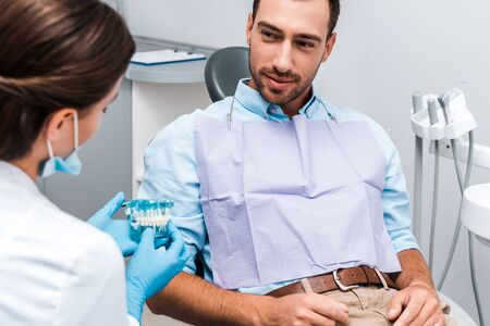 selective focus of handsome man looking at dentist holding teeth model in clinic