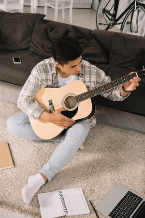 young asian man sitting on sofa at home and playing acoustic guitar Stok Fotoğraf