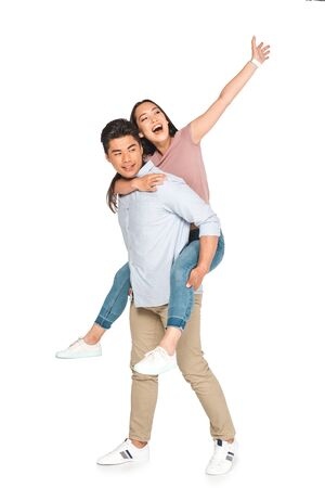 cheerful asian woman waving hand while piggybacking on happy boyfriend on white background Banco de Imagens