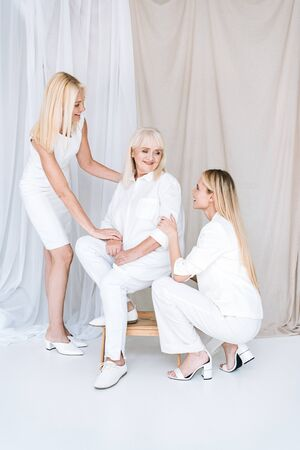 full length view of elegant blonde mother and daughter in total white outfits near senior woman on chair