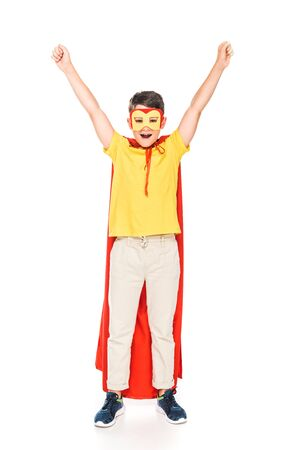 full length view of smiling kid in mask and hero cloak showing yes gesture isolated on white