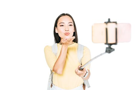 attractive asian woman sending air kiss while taking selfie on smartphone with selfie stick isolated on white