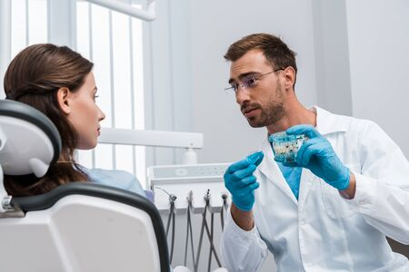 selective focus of attractive woman looking at handsome dentist in glasses holding tooth model