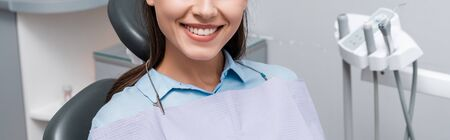 panoramic shot of cheerful woman smiling in dental clinic