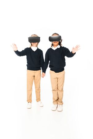 full length view of two multicultural schoolgirls holding hands while using virtial reality headsets on white background