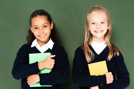 two cute multicultural schoolgirls smiling at camera while standing near chalkboard and holding books