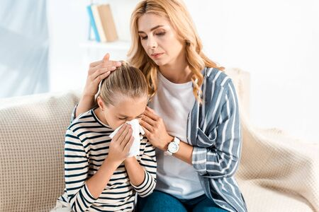 mother touching hair of sick daughter sneezing in tissue