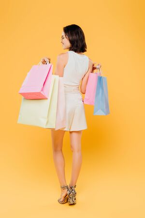 back view of stylish woman in sunglasses holding shopping bags isolated on yellow