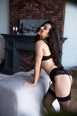 sexy girl in black underwear leaning on sofa and smiling with closed eyes while standing in living room
