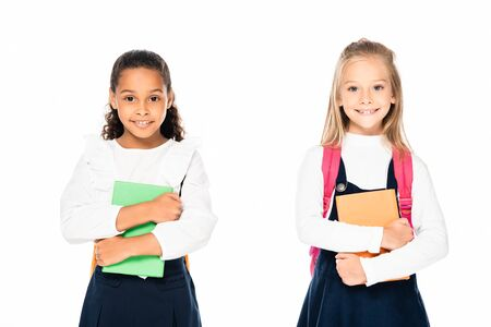 two cute multicultural schoolgirls holding books and smiling at camera isolated on white 写真素材 - 132007885