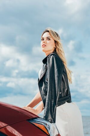 attractive and blonde woman in black jacket looking away Фото со стока