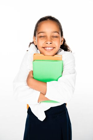 happy african american shoolgirl holding books and smiling with closed eyes on white background
