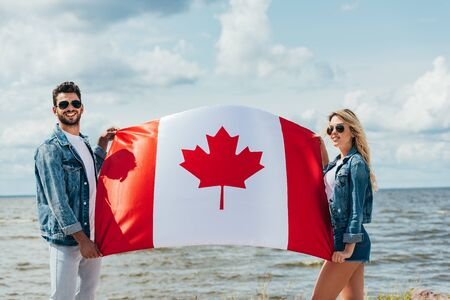 attractive woman and handsome man smiling and holding canadian flag