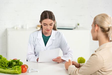dietitian in white coat holding paper and patient at table Stock fotó