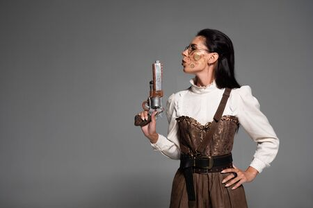 confident steampunk woman standing with hand on hip and holding pistol isolated on grey