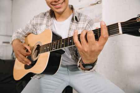 partial view of smiling young man playing acoustic guitar at home