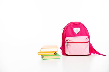 pink backpack with heart symbol and stack of books on white background with copy space Stock Photo