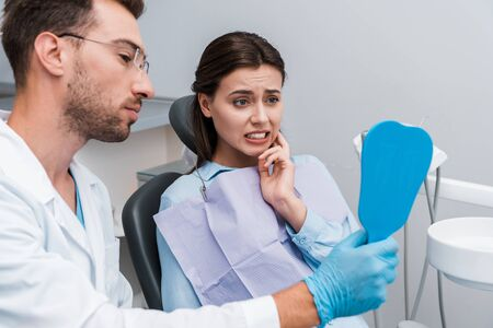 selective focus of girl looking in mirror and touching face near handsome dentist