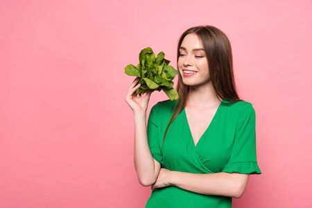 smiling young woman holding spinach with closed eyes isolated on pink