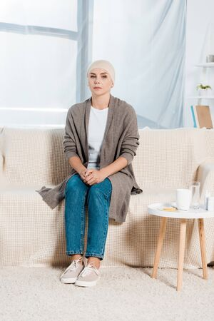 sick woman with cancer sitting on sofa near table