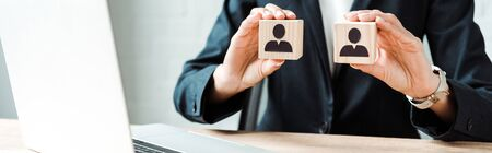 panoramic shot of businesswoman holding wooden cubes with human shapes near laptop Stock Photo