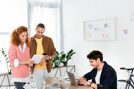 friends looking at digital tablet and man using laptop in office