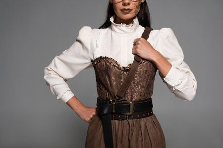 cropped view of steampunk woman with makeup standing with hand on hip isolated on grey Stock Photo