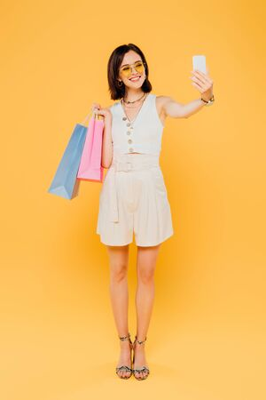 full length view of happy fashionable girl in sunglasses with shopping bags taking selfie on smartphone isolated on yellow Stok Fotoğraf