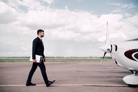 Ganzkörperansicht eines Geschäftsmannes in formeller Kleidung, der an einem sonnigen Tag Laptop und Ordner in der Nähe des Flugzeugs hält