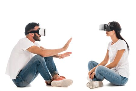 man gesturing near woman while using virtual reality headset on white