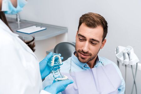 cropped view of dentist in medial mask and latex gloves holding teeth model near handsome patient