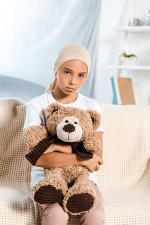 sick kid sitting on sofa and holding teddy bear