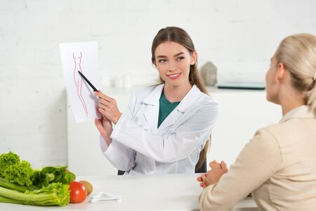 smiling dietitian in white coat showing paper with perfect body image to patient