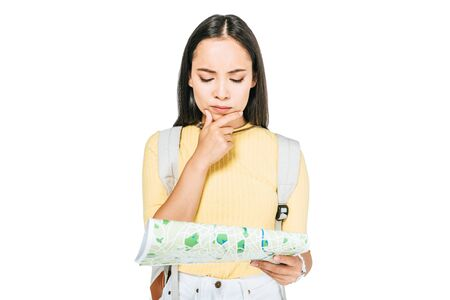 thoughtful asian girl holding hand near face while looking at map isolated on white