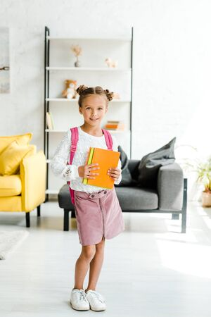 happy schoolgirl standing with backpack and holding books at home