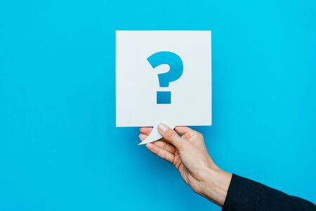 cropped view of woman holding speech bubble with question mark on blue Stockfoto