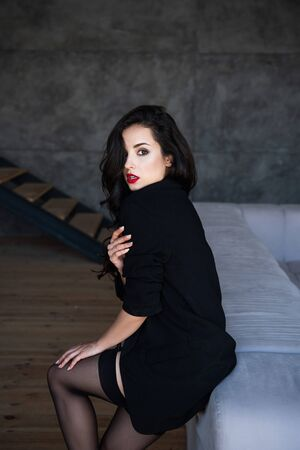 sexy girl with black jacket sitting on sofa and looking at camera