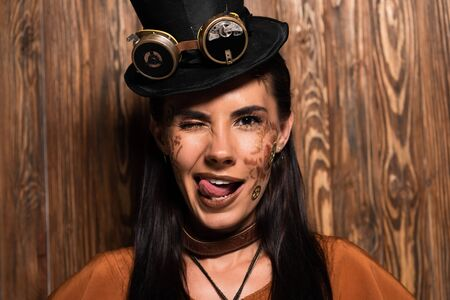 front view of smiling steampunk woman blinking and sticking out tongue on wooden