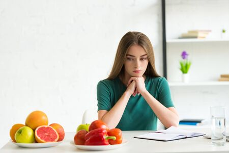 sad woman sitting at table with fresh fruits and vegetables