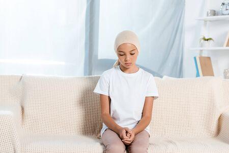 upset kid in head scarf sitting on sofa in living room Stockfoto - 132175837