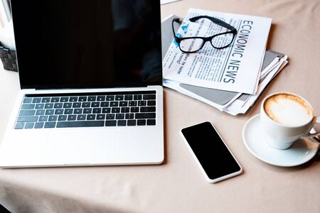laptop and smartphone with blank screen, cup of coffee, documents, newspaper and glasses on table in cafe
