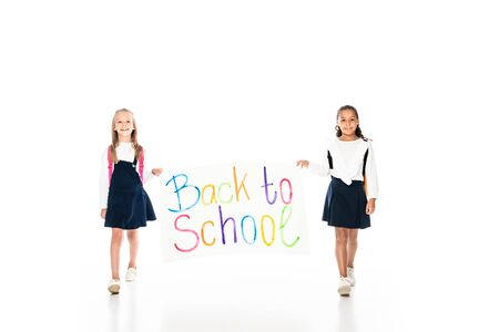 full length view of two multicultural schoolgirls holding placard with back to school inscription while walking on white background 写真素材 - 132008911