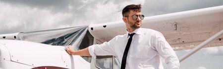 panoramic shot of confident pilot in sunglasses standing near plane Banco de Imagens