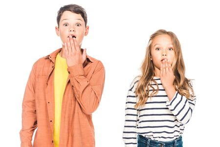 front view of shocked children covering mouths with hands isolated on white Imagens