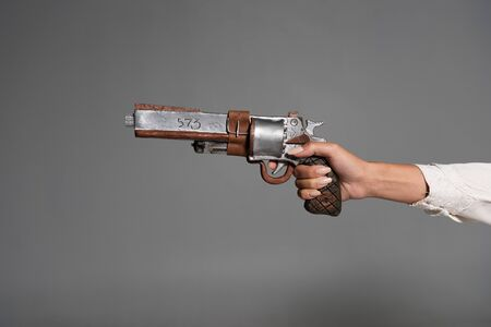 cropped view of woman holding vintage pistol isolated on grey