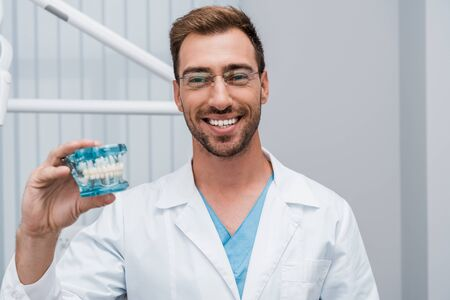 cheerful bearded dentist in glasses holding tooth model in dental clinic 写真素材