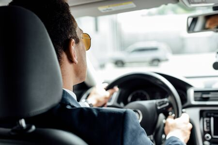 back view of african american businessman in suit and sunglasses driving car