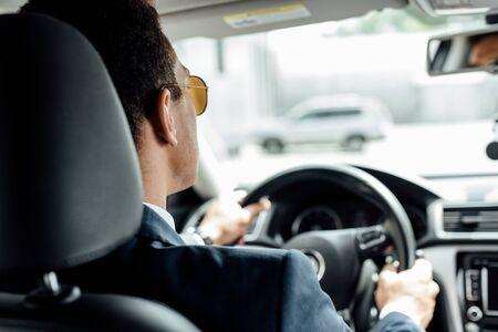 widok z tyłu afroamerykańskiego biznesmena w garniturze i okularach przeciwsłonecznych jeżdżącego samochodem